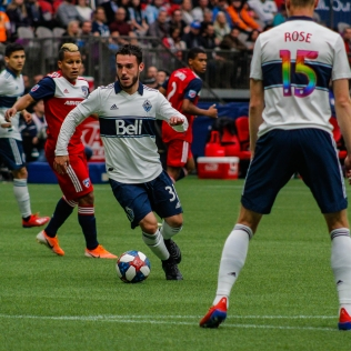 Russel Teibert dribbling with the ball in his own half against FC Dallas