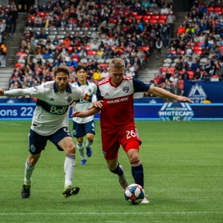 Jon Erice challenging FC Dallas' John Nelson for the Ball
